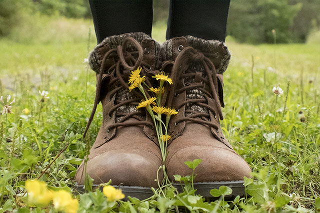 girls boots with flowers in field